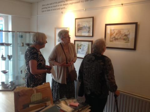 Artists Mary McGrath, Anne Cree and Ellen Smyth admire Wesley Lewis's paintings